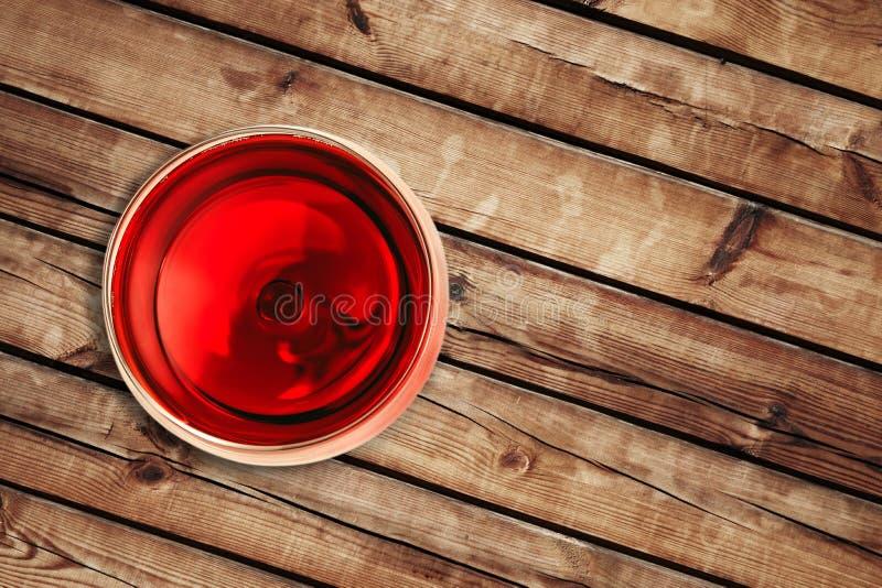 Överkant av sikten av rött vin i exponeringsglaset på wood bakgrund arkivbilder
