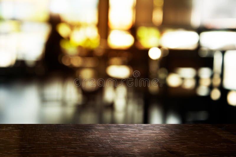 Överkant av svart tabellträ med suddighetsljus i stång eller restaurangen med mjuk ljus bakgrund royaltyfri foto