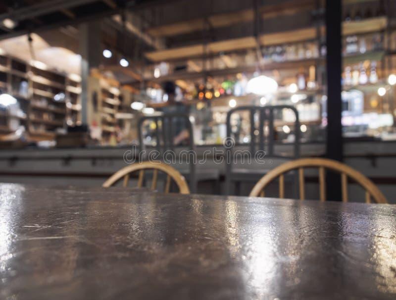 Överkant av tabellen och stol med suddig stångrestaurangbakgrund