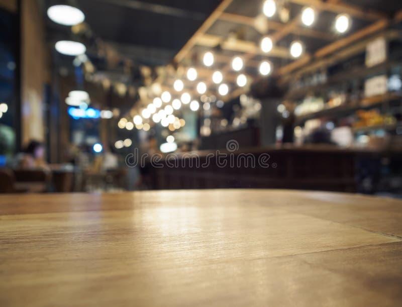 Överkant av trätabellen med suddig stångrestaurangbakgrund royaltyfria foton