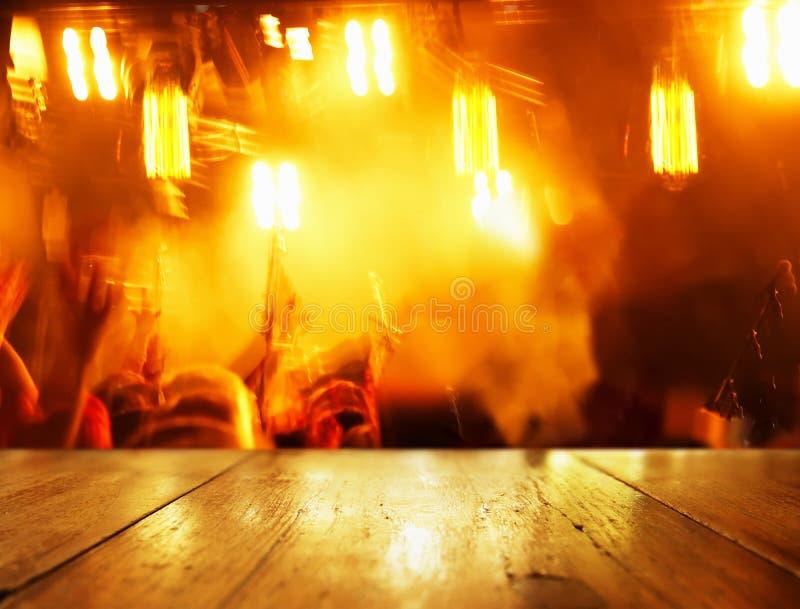 Överkant av wood bakgrund för tabell med orange ljus för suddighet av partiet in arkivfoton