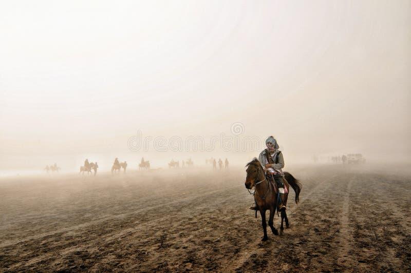 Överkant för Bromo indonesia hästridning av bergmolnet fotografering för bildbyråer