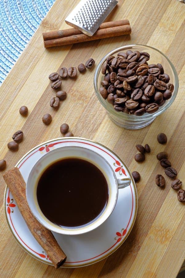 Överkant för stående för bönor för kaffekopp och för kanelbruna pinnar arkivfoton