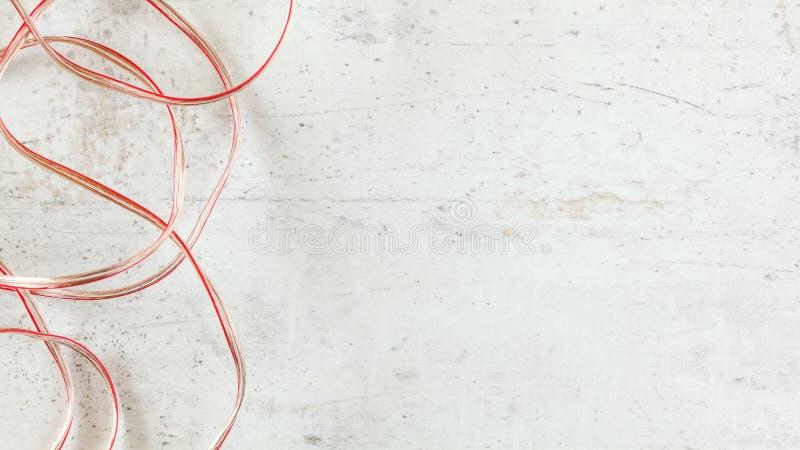 Överkant ner sikt - två röda trådar och genomskinlig kopparhögtalarekabel på det vita stenbrädeskrivbordet, brett baner med utrym royaltyfri foto