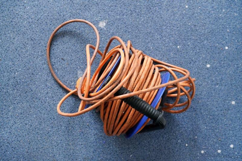 Överkant ner sikten, tilltrasslad orange ledning för maktkabelförlängning på blå rulle, över smutsig matta fotografering för bildbyråer