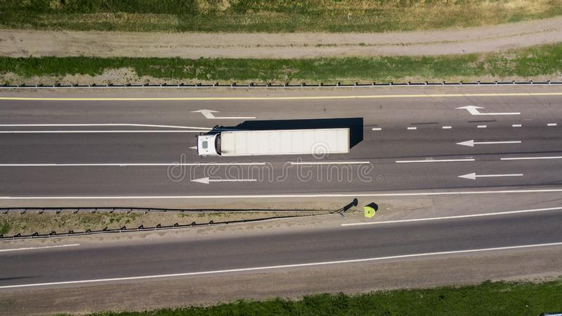 Överkant ner som är nära upp av vägen, asfalt, vitt piltecken som indikerar riktningen, väg av huvudvägen arkivfoton