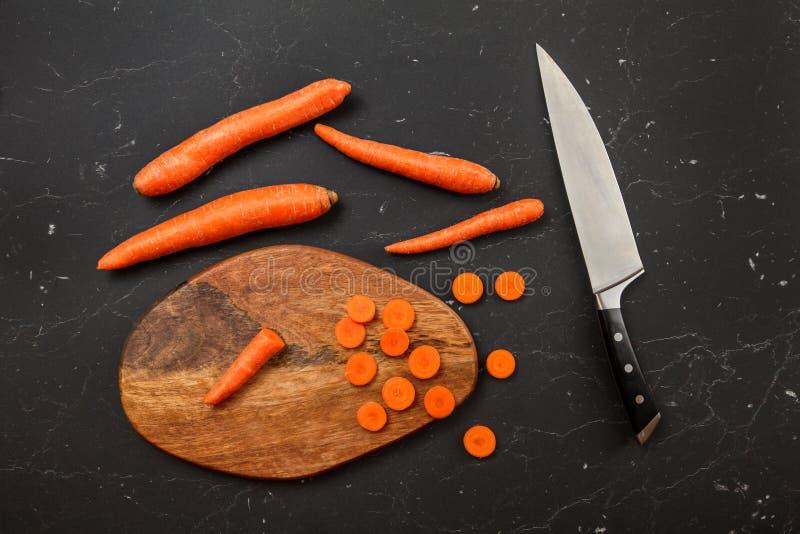 Överkanten ner sikt, kockkniven, morötter, några av dem skivade på skärbräda arkivfoto
