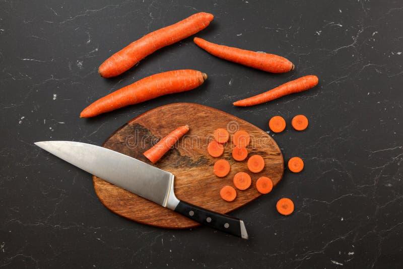 Överkanten ner sikt, skärbräda, kockkniven och morötter, några av dem klippte i små cirklar, på det svarta marmorskrivbordet royaltyfri fotografi