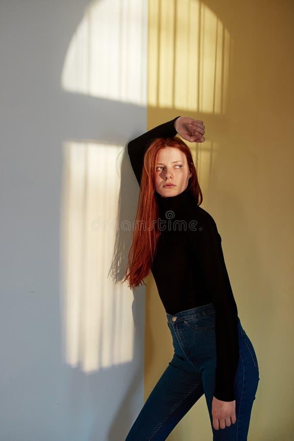 Överkanten och jeans för härlig flicka för rödhårig man långhårig poserar den iklädda svarta mot väggen med en reflexion av fotografering för bildbyråer