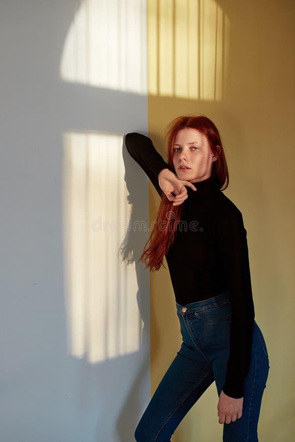 Överkanten och jeans för härlig flicka för rödhårig man långhårig poserar den iklädda svarta mot väggen med en reflexion av arkivbild