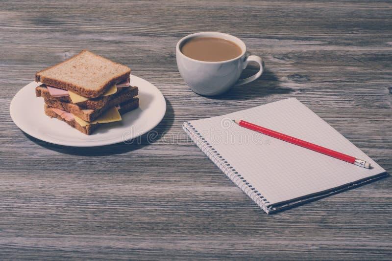 Överkanten ovanför fast utgiftsiktsphot av avbrottet vilar kopplar av mellanmålet på arbete Ostsmörgås med koppen av vitt kaffe,  arkivfoto