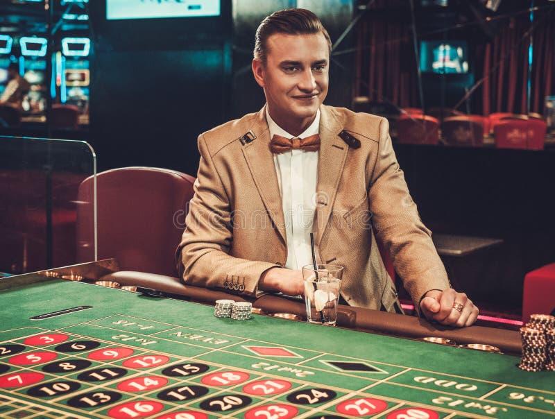 Överklassmandobbleri i en kasino royaltyfria foton