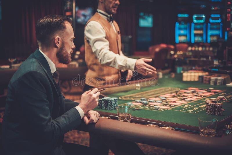 Överklassmandobbleri i en kasino arkivfoto