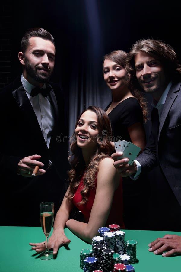 Överklassvänner som spelar i en kasino royaltyfri foto