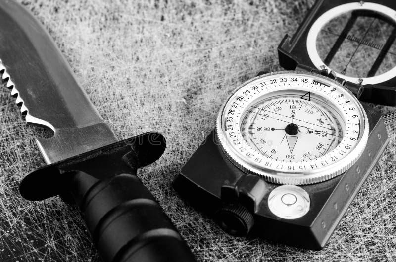 Överlevnadkniv och militärt kompassslut upp royaltyfri foto