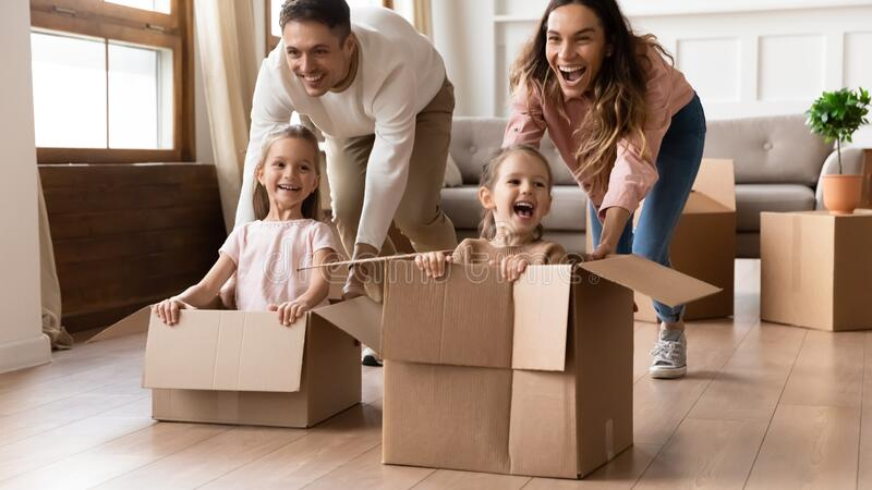 Överlycklig familj har kul på att flytta dag arkivbilder