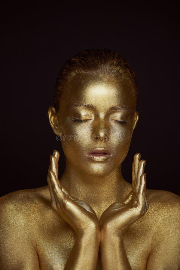 Övernaturliga guld- flickor för stående, händer nära framsidan Mycket delikat och kvinnligt Ögonen är stängda händer vikta in royaltyfria bilder