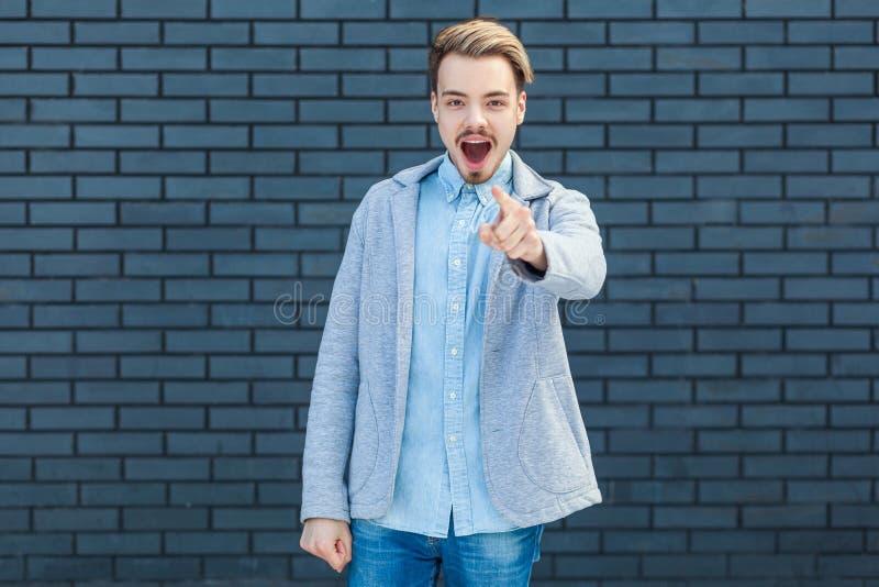 Överraska dess dig? otrolig nyheterna Stående av den chockade stiliga unga blonda mannen i tillfällig stil som står, pekar och se fotografering för bildbyråer