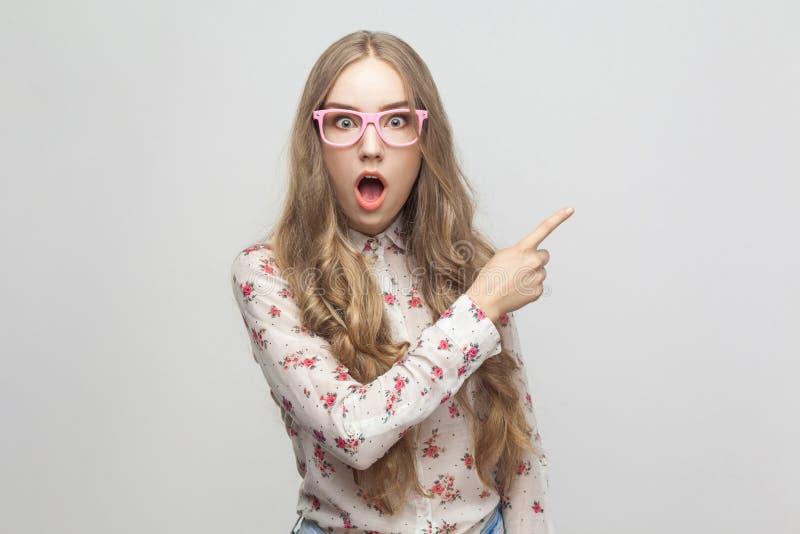 Överraska! Fantastisk nyheterna! Härlig ung vuxen flicka som visar fingret arkivfoton