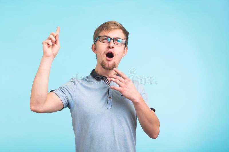 Överraska mig förstår det Förvånade unga manliga lönelyfter fingrar som minns något, isolerat över blå bakgrund reaktion fotografering för bildbyråer