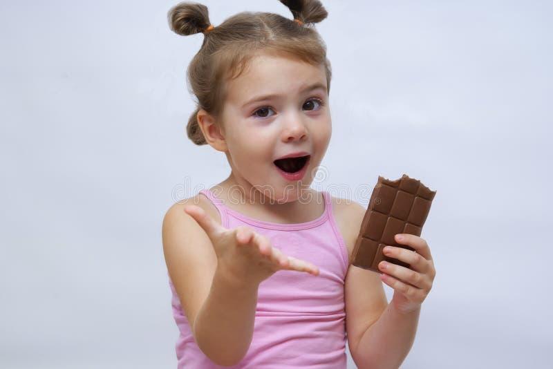 Överraskad rolig tjej med öppen mun som håller choklad och ser ut arkivbilder