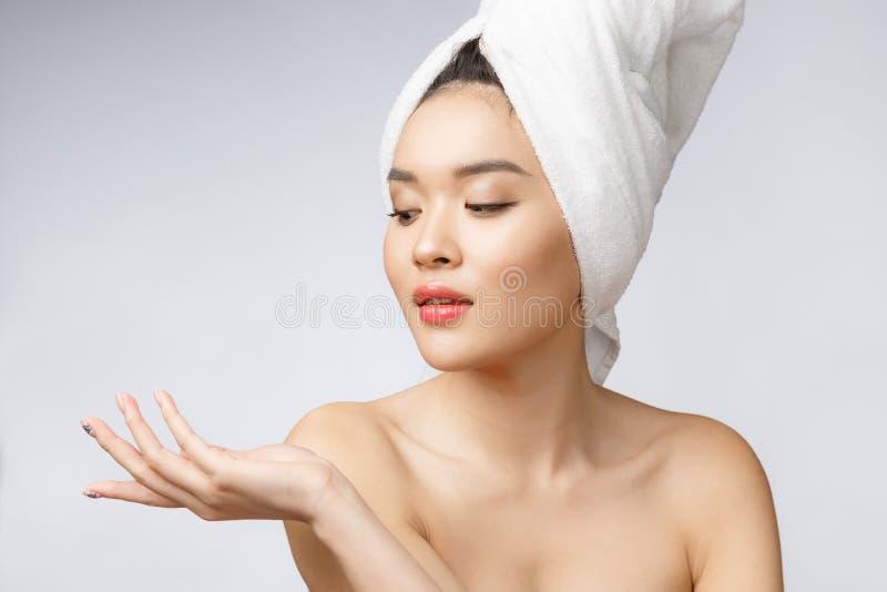Överraskar den härliga asiatiska kvinnan för ståenden förvånat, och peka handen till rätsidan på grå bakgrund, åtgärdar sinnesrör royaltyfri bild