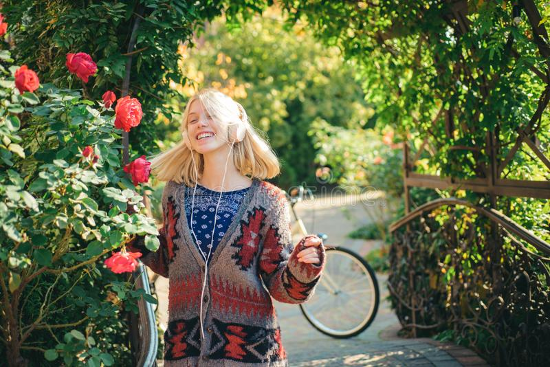 Överraskningkvinnadans med hörlurar Den lyckliga unga kvinnan förbereder sig för solig dag för höst härlig blond kvinna arkivfoton