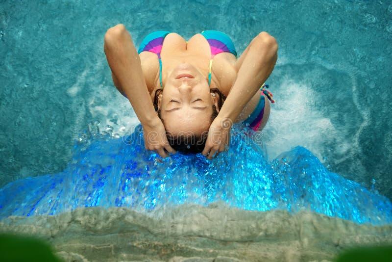 Översidasikt av en härlig ung sexig kvinna i bikini under det plaskande vattnet av vattenfallet i den Spa Wellnesspölen royaltyfri bild