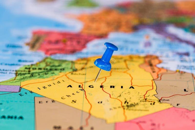 Översikt av Algeriet med en klibbad blå häftstift arkivbild