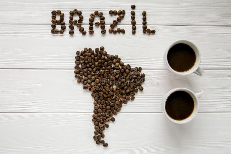 Översikt av Brasilien som göras av grillade kaffebönor som lägger på vit trätexturerad bakgrund två koppar kaffe royaltyfria foton