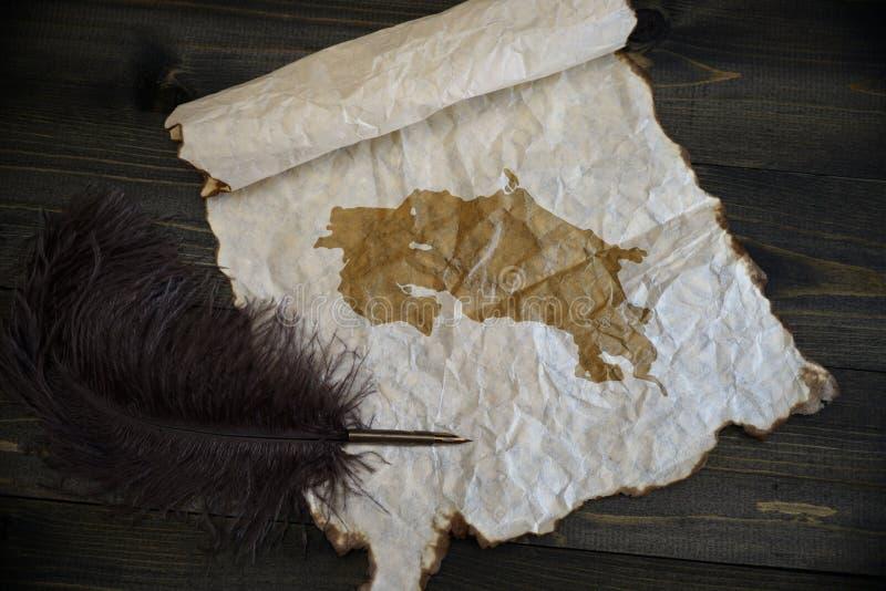 ?versikt av Costa Rica p? tappningpapper med den gamla pennan p? tr?texturskrivbordet royaltyfri foto