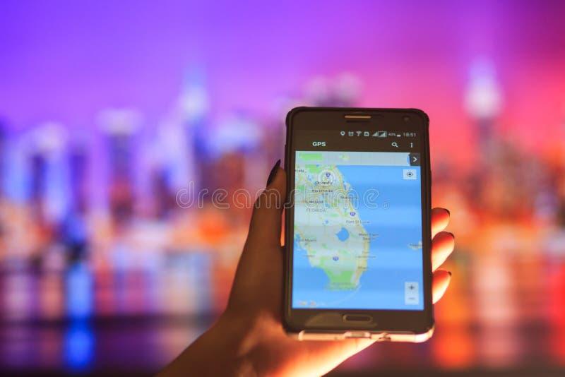 Översikt av Florida på telefonen i bakgrunden av en nattstad Slut upp av den hållande mobiltelefonen för kvinnahand royaltyfri bild