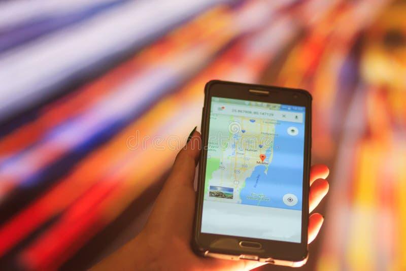 Översikt av Florida på telefonen i bakgrunden av en nattstad Slut upp av den hållande mobiltelefonen för kvinnahand royaltyfri fotografi