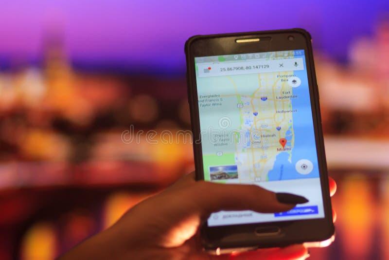 Översikt av Florida på telefonen i bakgrunden av en nattstad Slut upp av den hållande mobiltelefonen för kvinnahand royaltyfri foto