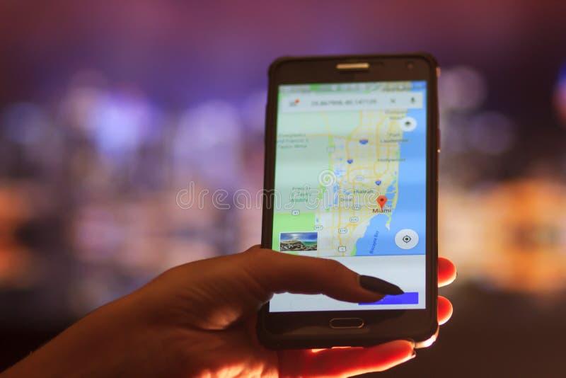 Översikt av Florida på telefonen i bakgrunden av en nattstad Slut upp av den hållande mobiltelefonen för kvinnahand arkivfoton