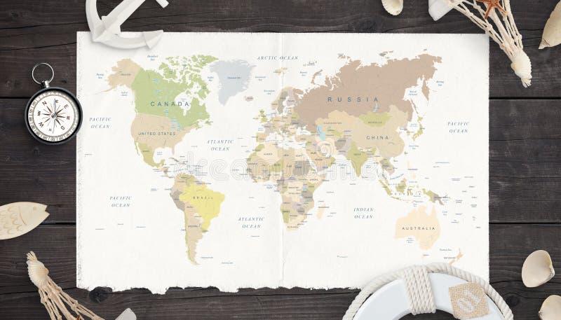 Översikt av världen på gammalt papper som omges av kompasset, ankaret, lifebelten och skal royaltyfri fotografi