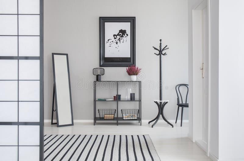 Översikt i svart ram på den gråa väggen av korridoren med spegeln, hyllan, hängaren och hår royaltyfri foto