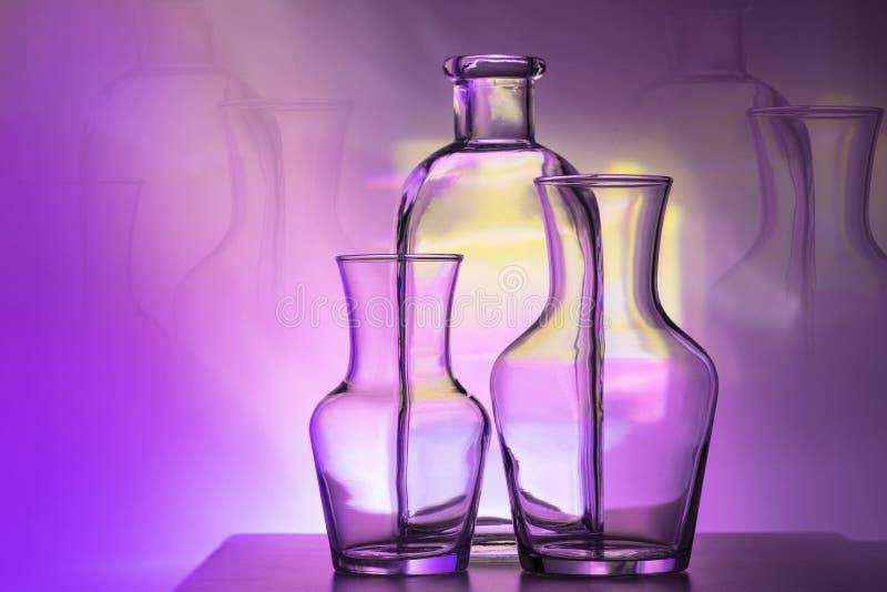 Översikten av två exponeringsglasvaser och flaskor på en ljus purpurfärgad och gul kulör bakgrund, horisontalorientering arkivfoto