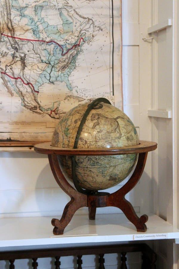 Översikter och jordklot med andra historiska objekt som visar liv och uppfinningar på Oneida Community Mansion House, Oneida New  arkivbilder