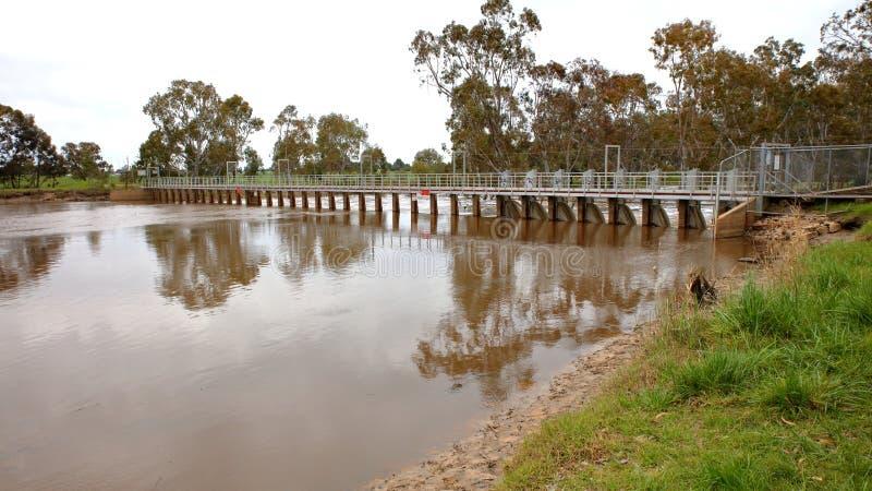 Översvämmad flod över dammbyggnaden arkivbilder