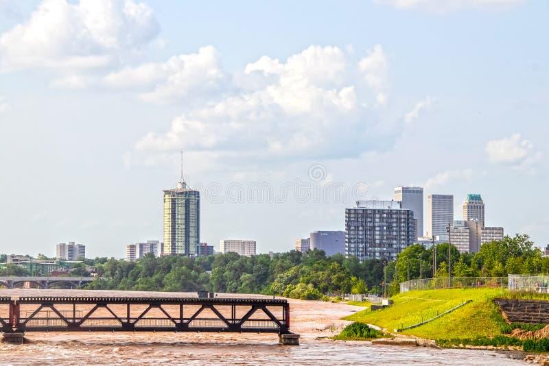 Översvämmade Arkansas River med gammal järnväg vände den fot- bron och den 21st gatabron och stadshorisont in royaltyfri foto