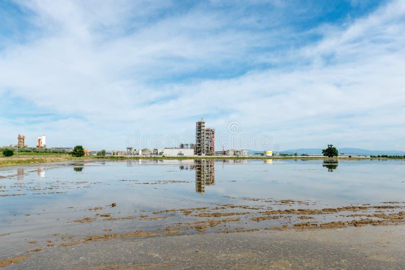 Översvämmade risfält med oljeraffinaderiet, Lomellina (Italien) arkivfoton