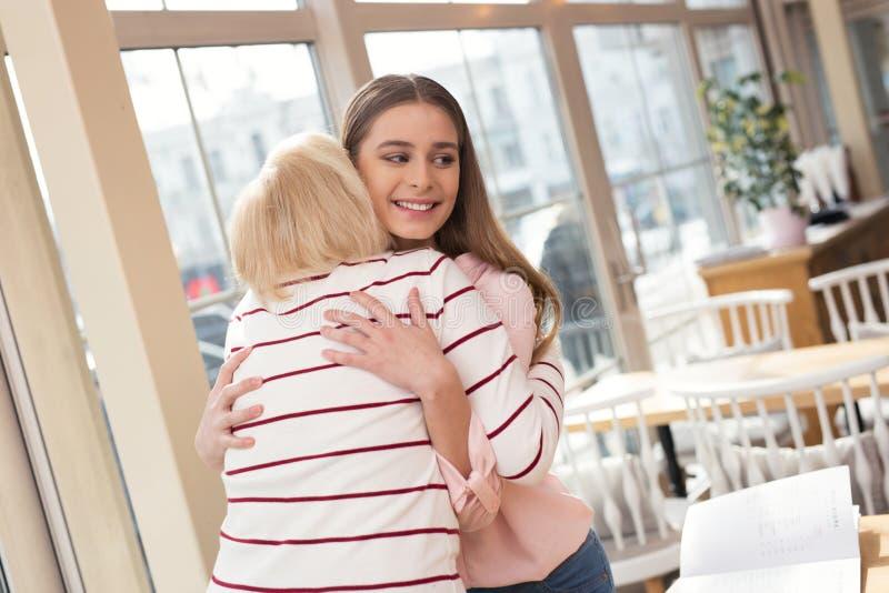 Översvallande flicka som kramar hennes farmor royaltyfria foton