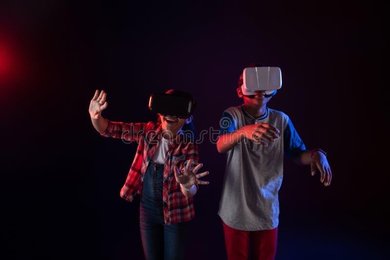 Översvallande ungar som bär VR-hörlurar med mikrofon royaltyfria bilder