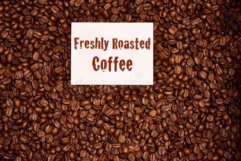 Överträffa ner av kaffebönor med det nytt grillade kaffetecknet royaltyfri foto