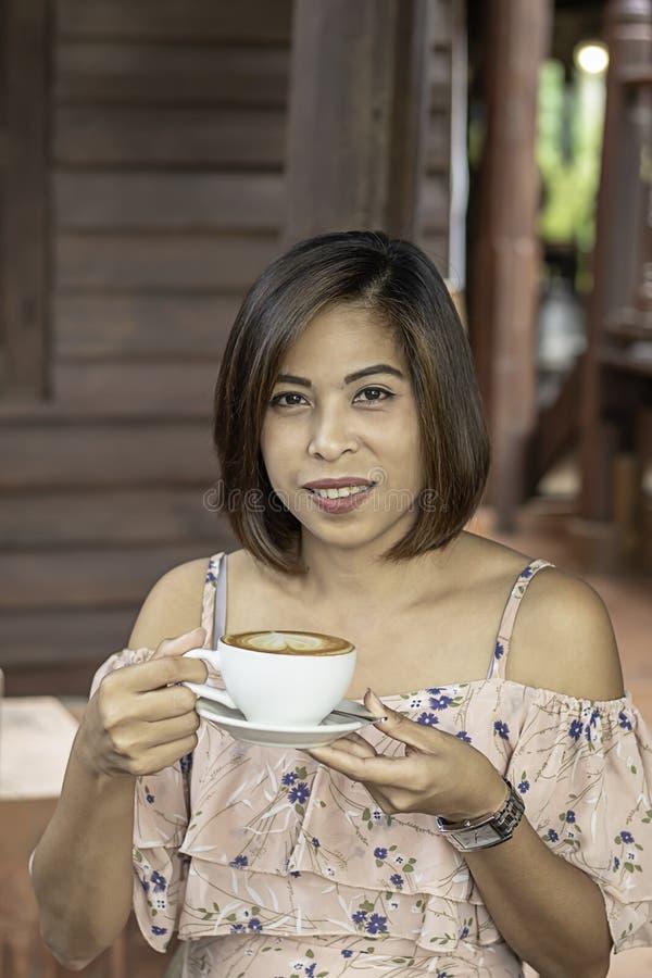 Överträffade den asiatiska kvinnan för handen som rymmer varm kaffeespresso, med hjärta-formad mjölkar i vitt exponeringsglas royaltyfri foto