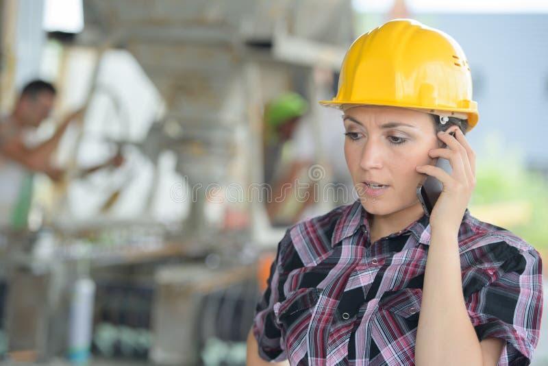 Övervaka den kvinnliga teknikern för elektrifiering genom att använda mobiltelefonen royaltyfria bilder