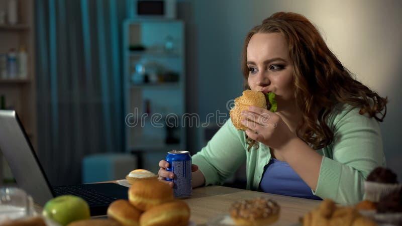 Överviktig dam som äter sjuklig mat, hållande ögonen på show på bärbara datorn, stillasittande liv royaltyfri fotografi