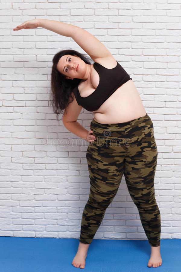 Överviktig fet ung kvinna som gör lutningar på mattt hemmastatt Kondition, arkivfoto