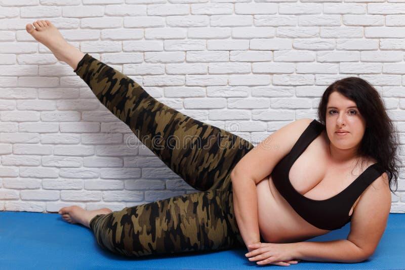 Överviktig fet utbildning för ung kvinna lägger benen på ryggen på mattt hemmastatt Kondition royaltyfria foton